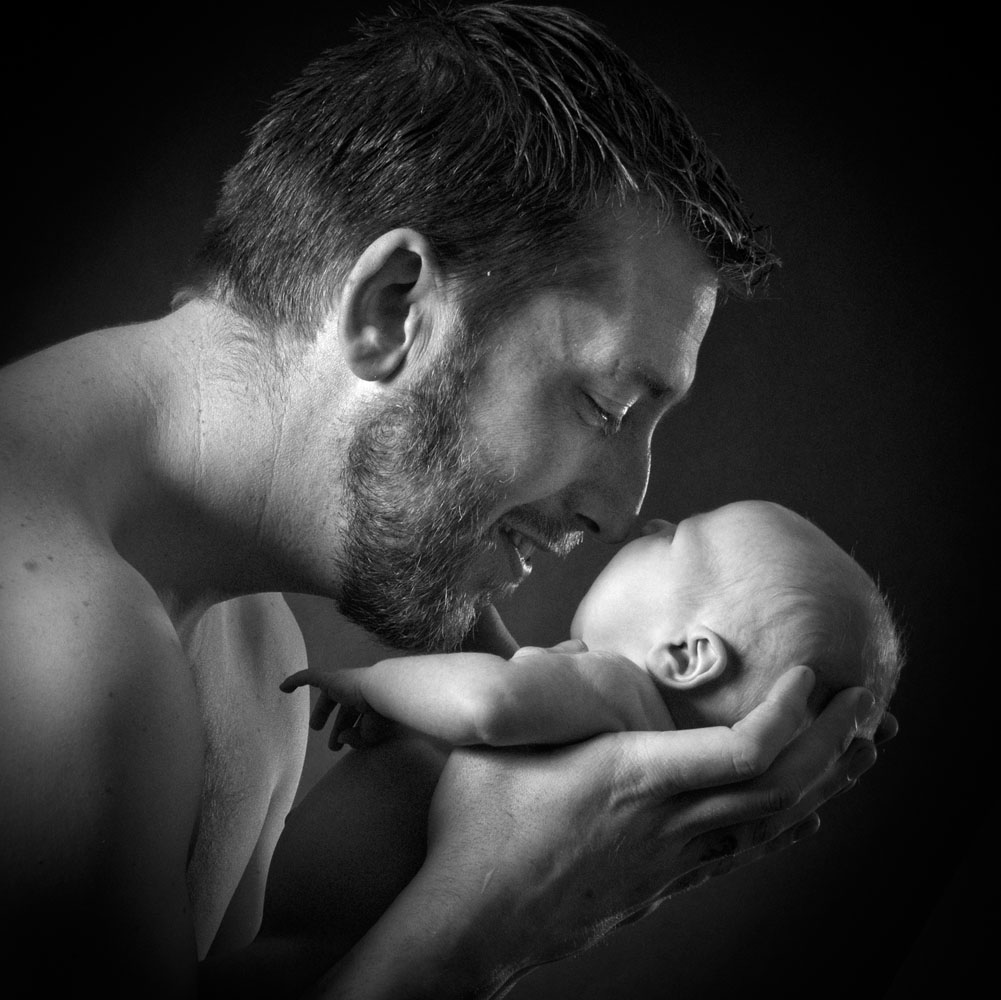 Niestadt-Fotografie-Schoonhoven-Newborn-shoot-vader-met-dochter-sfeervol-tegen-een-donkere-achtergrond-neusjes-tegen-elkaar