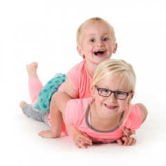 Niestadt-fotografie-Schoonhoven-studio-shoot-met-twee-zusjes-samen-liggend-op-een-witte-achtergrond