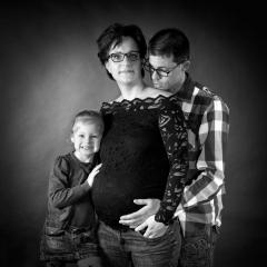 Niestadt-Fotografie-Schoonhoven-zwangerschaps-shoot-sfeervol-licht-tegen-zwarte-achtergrond-in-zwart-wit-met-vader-en-dochter